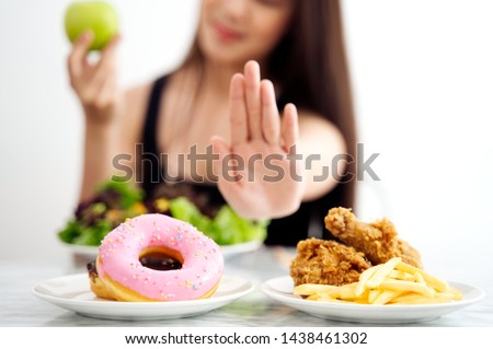 Young girl on dieting for good health concept. Close up female using hand reject junk food by pushing out her favorite sweet donuts and fried chicken and choose green apple and salad for good health. #1438461302