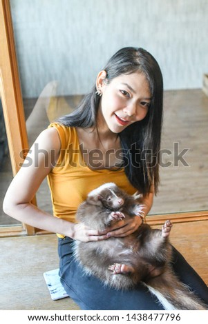 Young beautiful asian lady holding pet skunk