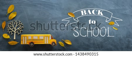 education and back to school. Top view photo of cardboard bus next to autumn dry leaves over classroom blackboard background