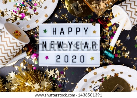 Happy new year 2020 table with modern light box with party cup,party blower,tinsel,confetti.Fun Celebration holiday party time table flat lay invitation or greeting card.new year eve concept #1438501391