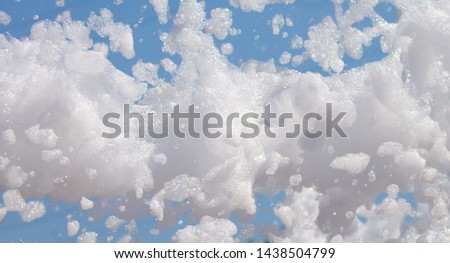 White soap foam on a blue sky background. Fun foam, background or texture of a white foam with copy space Entertainment foamy parties a summer entertainment festival in the water park #1438504799