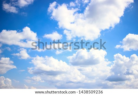 Deep blue skies with white clouds background with space for text,  blue cloudy skies texture, dark blue sky wallpaper with with white fully clouds and sunlight Royalty-Free Stock Photo #1438509236