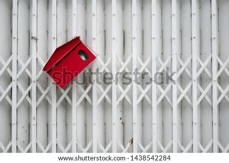 Tilted red mail box on white metal gate #1438542284