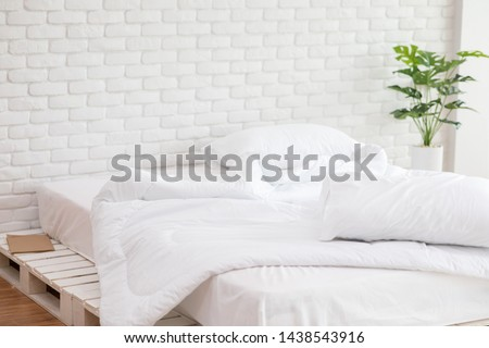 Messed bed with white pillow and blanket with natural light in bedroom in the morning,Messy bed after wake up,Messy bed and Cozy Bedroom Concept #1438543916