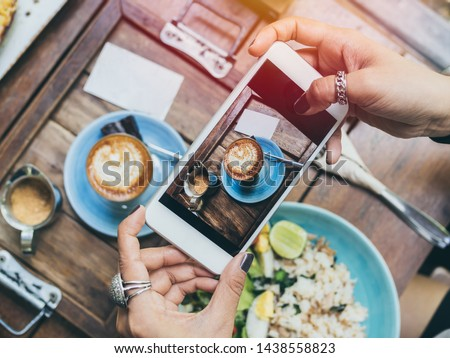 Woman's hands taking photo of coffee cup, Piccolo Latte, brownies with breakfast on wooden table by smartphone, top view.