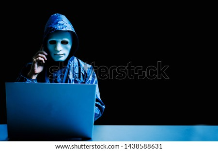 Anonymous computer hacker in white mask and hoodie. Obscured dark face using laptop computer for cyber attack and calling on cellphone, Data thief, internet attack, darknet and cyber security concept. #1438588631
