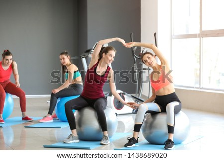 Young sporty women doing exercises with fitballs in gym #1438689020