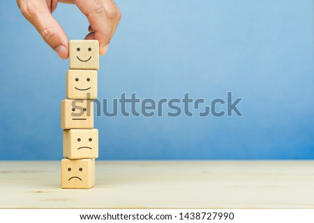 Customer service evaluation and satisfaction survey concepts. The client's hand picked the happy face smile face symbol on wooden blocks, copy space Royalty-Free Stock Photo #1438727990