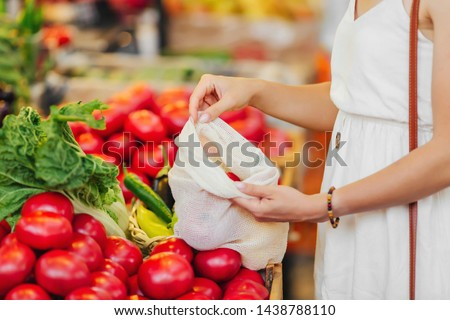 Female hands puts fruits and vegetables in cotton produce bag at food market. Reusable eco bag for shopping. Zero waste concept. Royalty-Free Stock Photo #1438788110
