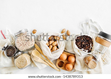 Nuts, dried fruits and  groats  in eco cotton bags and glass jars on white table in the kitchen. Zero Waste Food Shopping.  Waste-free living Royalty-Free Stock Photo #1438789313
