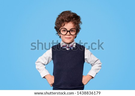Adorable little boy in nerdy glasses and school uniform keeping hands on waist and looking at camera against blue background