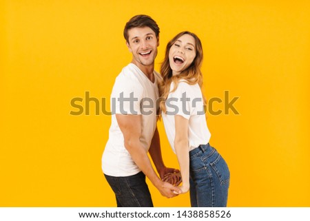 Portrait of amazing couple man and woman in basic t-shirts smiling and looking at camera while holding hands isolated over yellow background #1438858526