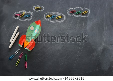 education. Back to school concept. rocket cut from paper and painted over blackboard background. top view, flat lay