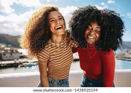 Two beautiful young women enjoying on the beach. Female friends walking on the beach and laughing on a summer day. Royalty-Free Stock Photo #1438920194