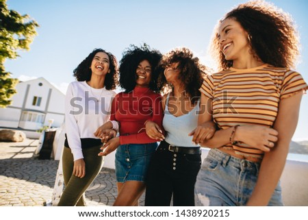 Mixed raced group of female friends walking together outdoors. Young women having fun outdoors at the beach. #1438920215