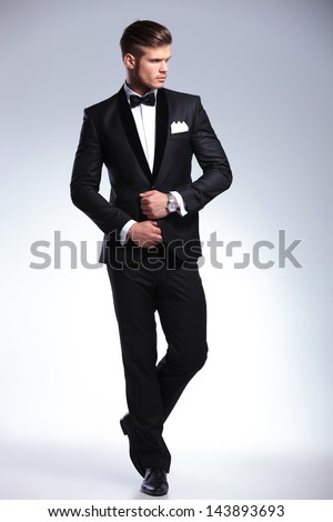 full length picture of an elegant young fashion man adjusting his tuxedo while looking to his side, away from the camera. on gray background Royalty-Free Stock Photo #143893693