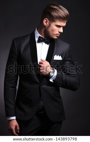 elegant young fashion man in tuxedo holding his hand on his jacket and looking to his side, away from the camera.on black background #143893798