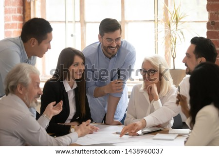 Happy diverse business team young and old workers talking brainstorming on project gathered at table, positive employees group engaged in teamwork working together at friendly staff corporate meeting #1438960037