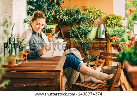 Young beautiful woman relaxing on cozy balcony, reading a book, wearing warm knitted pullover, glass of wine on wooden table #1438974374