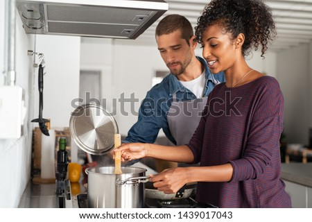 Portrait of happy young couple cooking together in kitchen at home. Woman cooking in pot with her boyfriend in kitchen. Man in apron helping his girlfriend preparing dinner. #1439017043