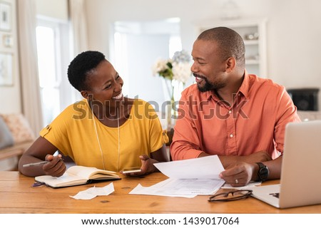 Mature couple sitting and managing expenses at home. Happy african man and woman paying bills and managing budget. Black smiling couple checking accountancy and bills while looking at each other. #1439017064