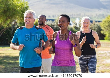 Healthy group of mature people jogging on track at park. Happy senior couple running at park with african friends. Multiethnic middle aged friends exercising together outdoor. Royalty-Free Stock Photo #1439017070