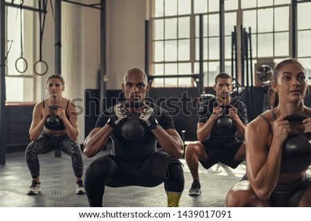 Fitness women and determined men exercising with kettlebell at gym. Group of young people doing a kettle bell exercise with squatting. Multiethnic group doing crouch exercise while holding weight. #1439017091