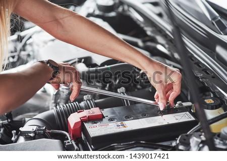 Replacing the battery. Car addicted woman repairs black car indoors in garage at daytime. #1439017421