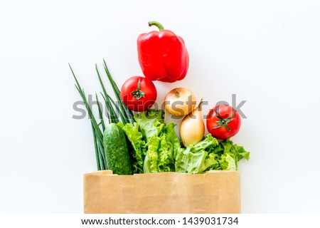 Buying fresh vegetables in paper bag on white background top view #1439031734
