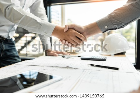 Architect and engineer construction workers shaking hands while working for teamwork and cooperation concept after finish an agreement in the office construction site, success collaboration concept  #1439150765