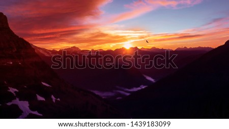 Epic Mountain Sunset Over Glacier National Park High Altitude Range of Peaks With Eagle Flying In Distance #1439183099