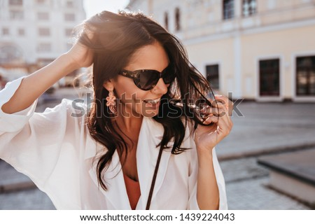 Amazing brunette woman in trendy earrings smiling on city background. Wonderful tanned girl in sunglasses enjoying good day. #1439224043