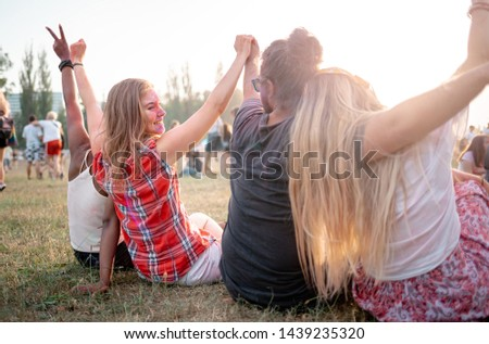 Group of multiethnic people sitting on grass ang having fun at summer music fetival #1439235320