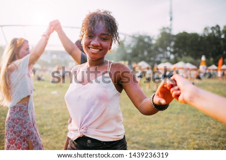 African American young woman with friends dancing at summer holi festival #1439236319