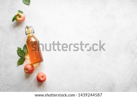 Apple cider vinegar or fermented fruit drink and organic apples on white, top view, copy space. Healthy eating and lifestyle concept. #1439244587