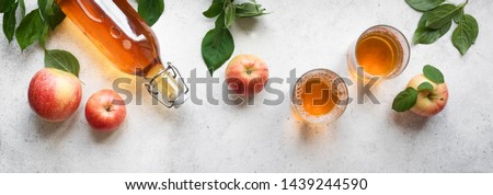 Apple cider drink or fermented fruit drink and organic apples on white, top view, banner. Healthy eating and lifestyle concept. #1439244590