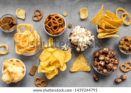 Assortment of Unhealthy Snacks: chips, popcorn, nachos, pretzels, onion rings in bowls, top view, copy space. Unhealthy eating concept. Royalty-Free Stock Photo #1439244791