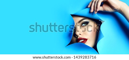 The face of a young beautiful girl with bright makeup and plump red lips looks into the hole in blue paper. Fingers with natural color varnish. #1439283716