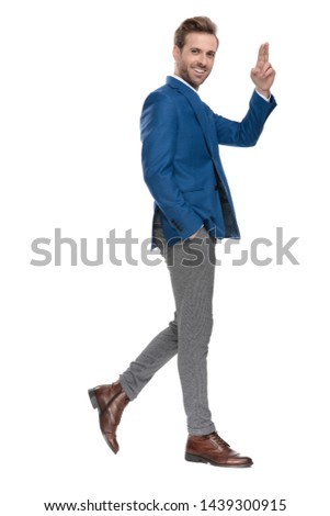 Side view of handsome casual guy greeting and holding his hand in his pocket while stepping and wearing an elegant suit on white studio background #1439300915