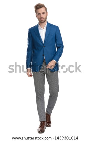 Serious looking casual man confidently walking forward while wearing an elegant suit on white studio background #1439301014