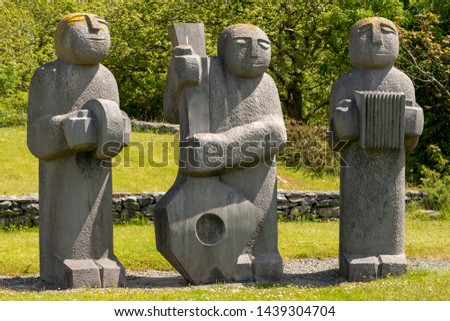 """Kenmare, County Kerry, Ireland. 18 June 2019. """"The Three Musicians"""" statue by the Irish sculptor Dick Joynt in River Park Kenmare Bay. The place is popular spot among the locals and tourists. #1439304704"""