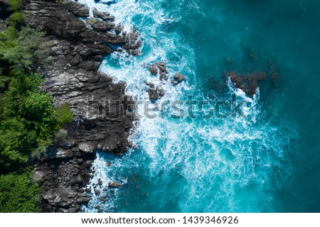 Aerial drone top view of ocean's beautiful waves crashing on the rocky island coast Royalty-Free Stock Photo #1439346926