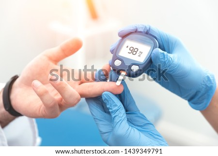 Doctor checking blood sugar level with glucometer. Treatment of diabetes concept. #1439349791