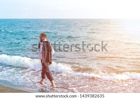 Successful businessman walk along the sea coast. Vacation concept #1439382635