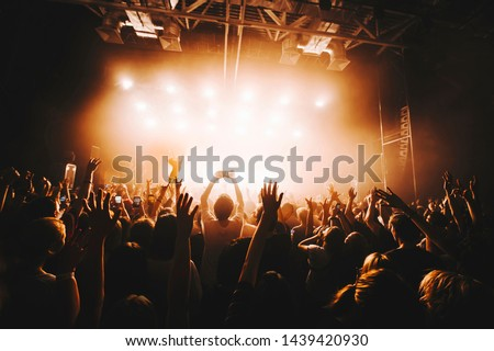 silhouette of the soloist standinf in a fog in the rays of light. concert crowd in front of bright stage lights. Dark background, smoke, concert  spotlights #1439420930