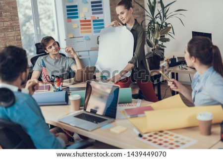 Team of employees gathering in meeting room while woman showing whatman paper with smile. Colleagues looking at her with interest #1439449070