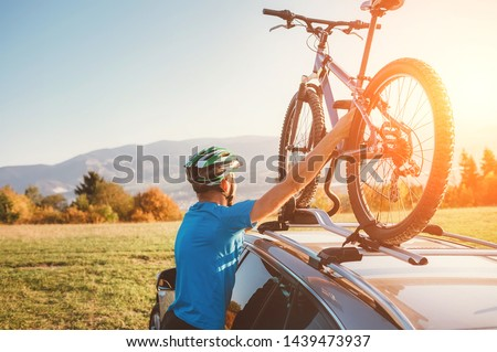 Mountain biker man take of his bike from the car roof Royalty-Free Stock Photo #1439473937