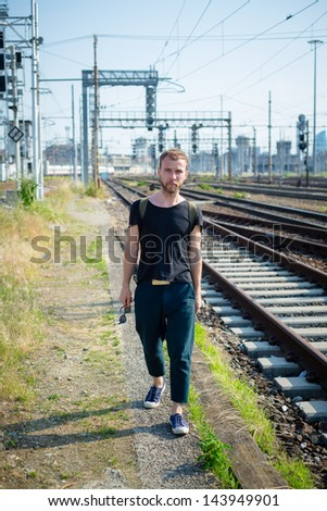 hipster modern stylish blonde man on rails in daily life #143949901