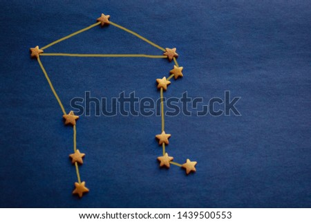 Constellation Libra, an astrological sign born in October. Gold stars on a blue background. Copy space, daylight. The picture is made by the author.