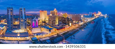 Aerial panorama of Atlantic city along the boardwalk at dusk. In the 1980s, Atlantic City achieved nationwide attention as a gambling resort and currently has nine large casinos. Royalty-Free Stock Photo #1439506331